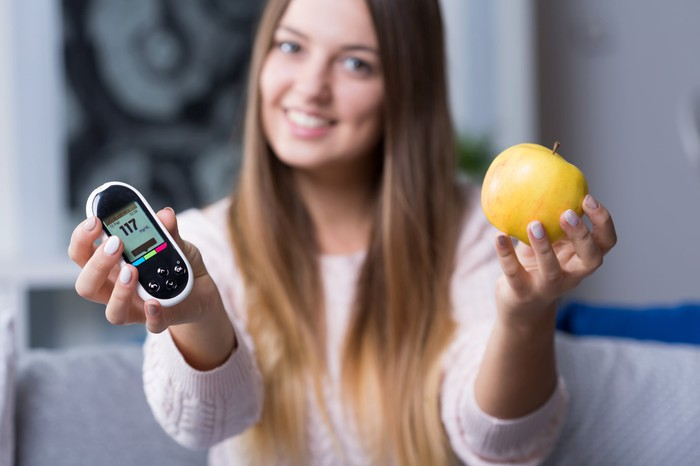 Woman with handheld glucose monitor in one hand and an apple in the other hand.