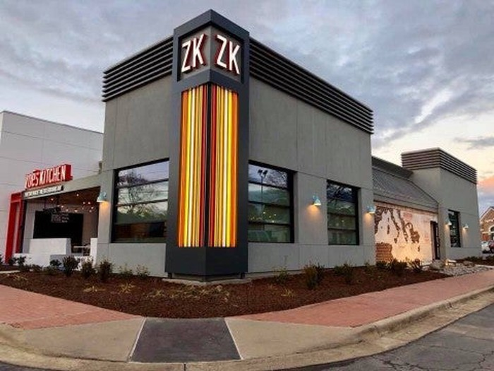 The outside of Zoe's Kitchen's new store in North Carolina. The building is modern minimalist, with orange lighting running up the corner of the building, and a new ZK logo at the top.