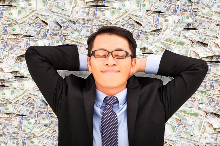 A man in business attire lies on a pile of cash, as he smiles with his eyes closed, head resting on his hands.