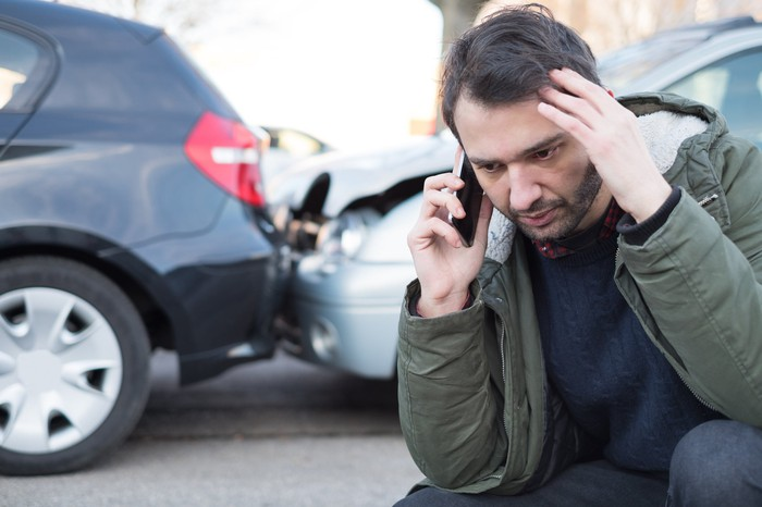 Man kneeling and talking on the phone in front of crashed cars.