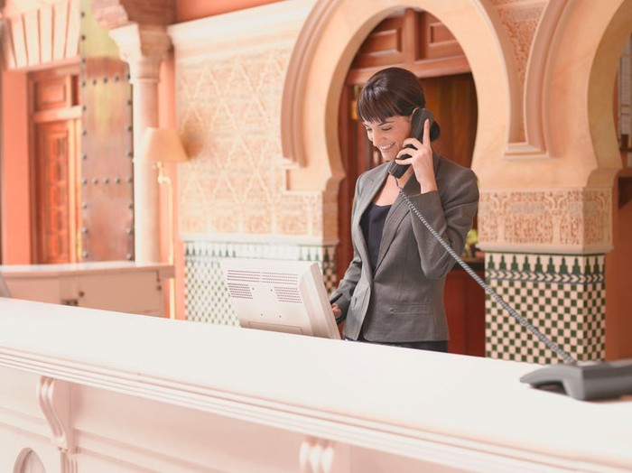 Hotel receptionist smiling and talking on phone at ornate reception desk.