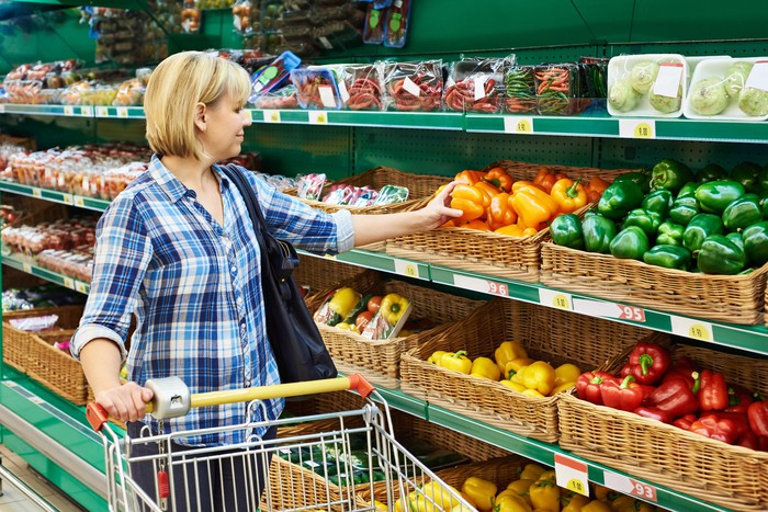Woman picking up pepper in grocery store produce section