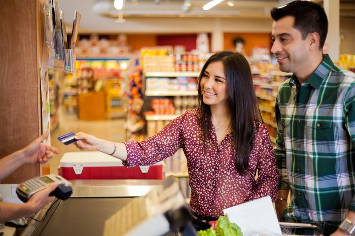 Couple using a credit card to pay for purchases in a grocery store.