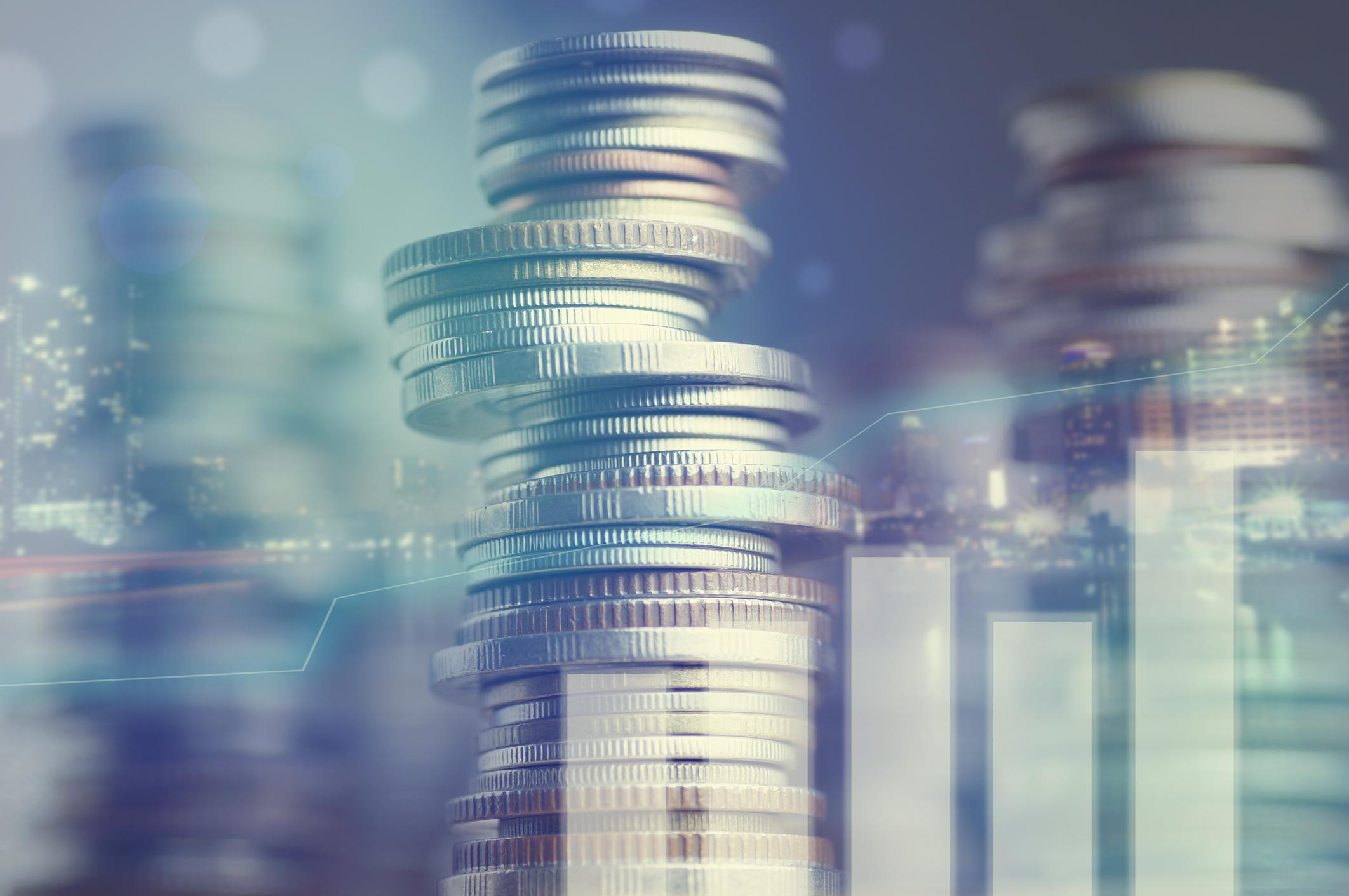 Stacks of coins behind a bar graph.