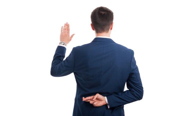 A businessman makes a promise, but crosses his fingers behind his back.