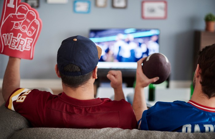 Two men watch football on TV.
