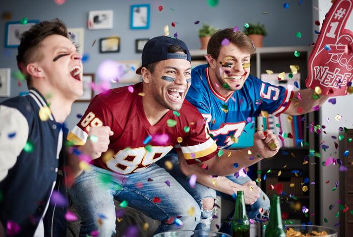 Men in football jerseys cheering