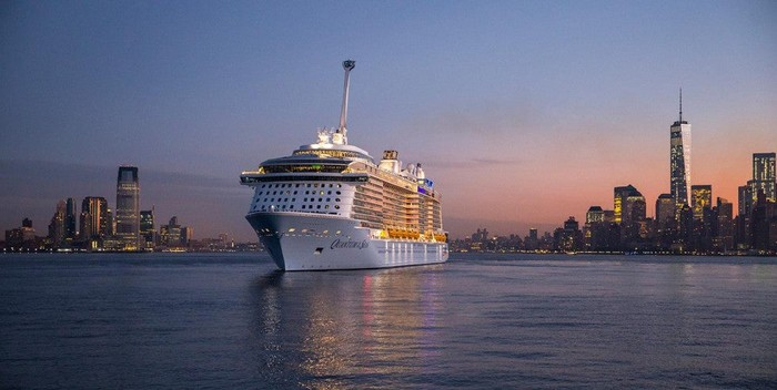 A cruise ship in a bay with a city skyline in the background.