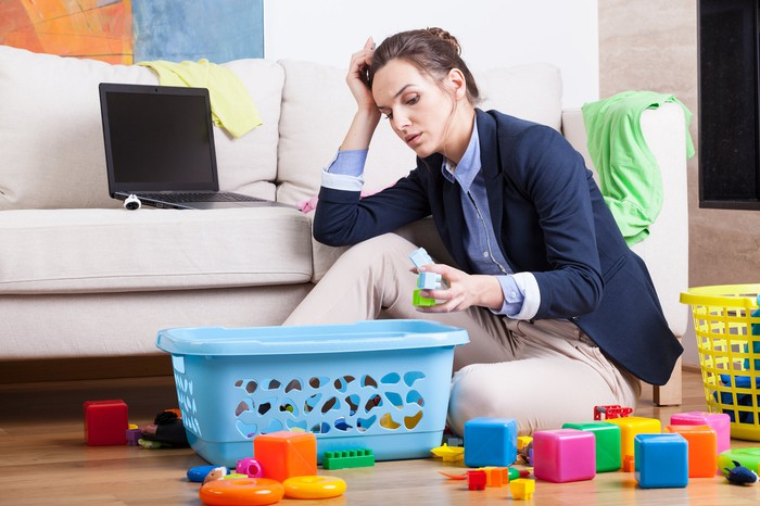 Professionally dressed woman sitting on the floor, cleaning up toys