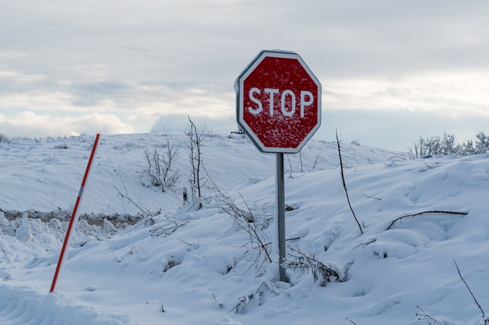 Image shows a stop sign in the snow.