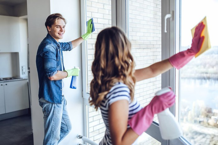 Young couple cleaning windows in apartment with household cleaning products.