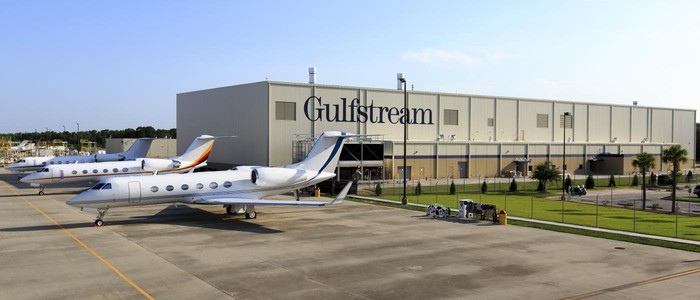 Gulfstream production facility with several business jets parked outside on a clear sunny day.