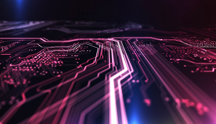 Computer circuit board illuminated in red and blue.