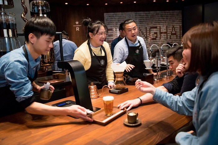 Starbucks baristas serve customers in the Shanghai Roastery.