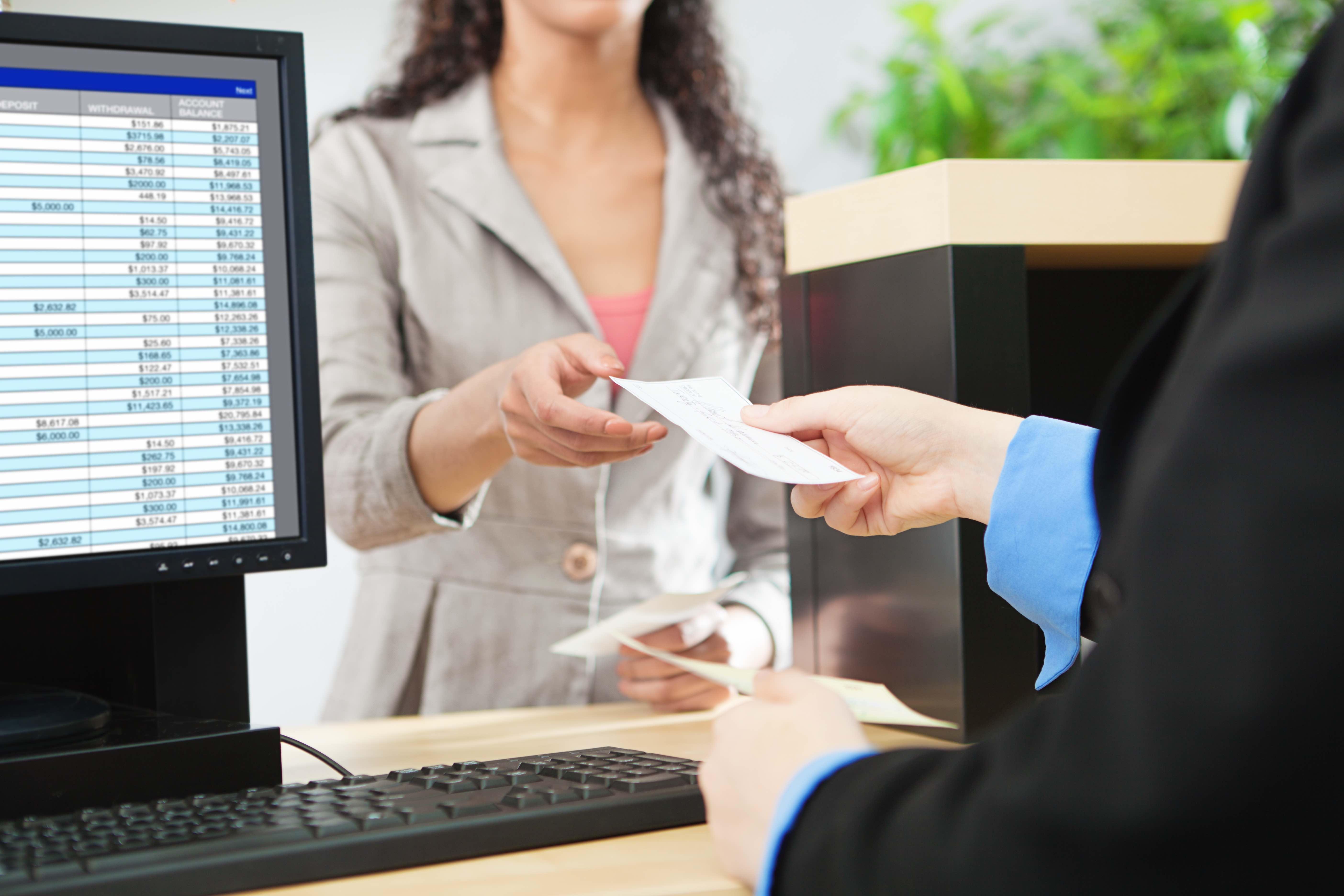 A teller handing a customer a check.