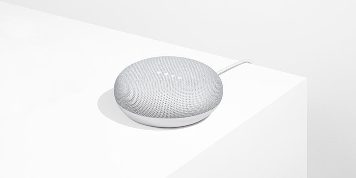 Google Home Mini smart speaker on a white surface