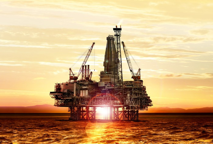 An offshore oil platform with the sun bursting through.