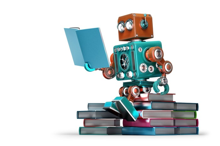 Robot reading a book while sitting on stack of books