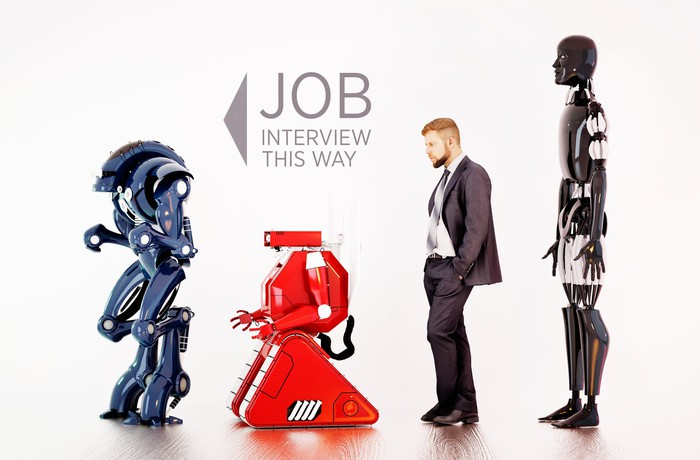 Robots and man in job interview line