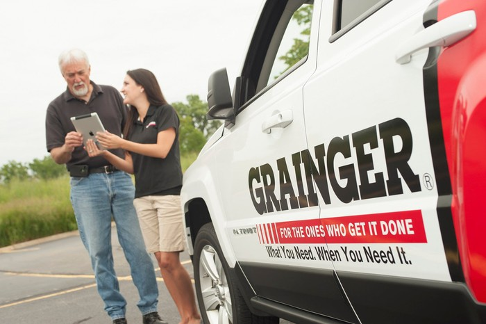 Two people standing in a parking lot next to a truck with the Grainger logo on it.