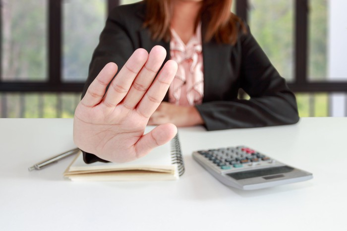An accountant signaling no with her hand.