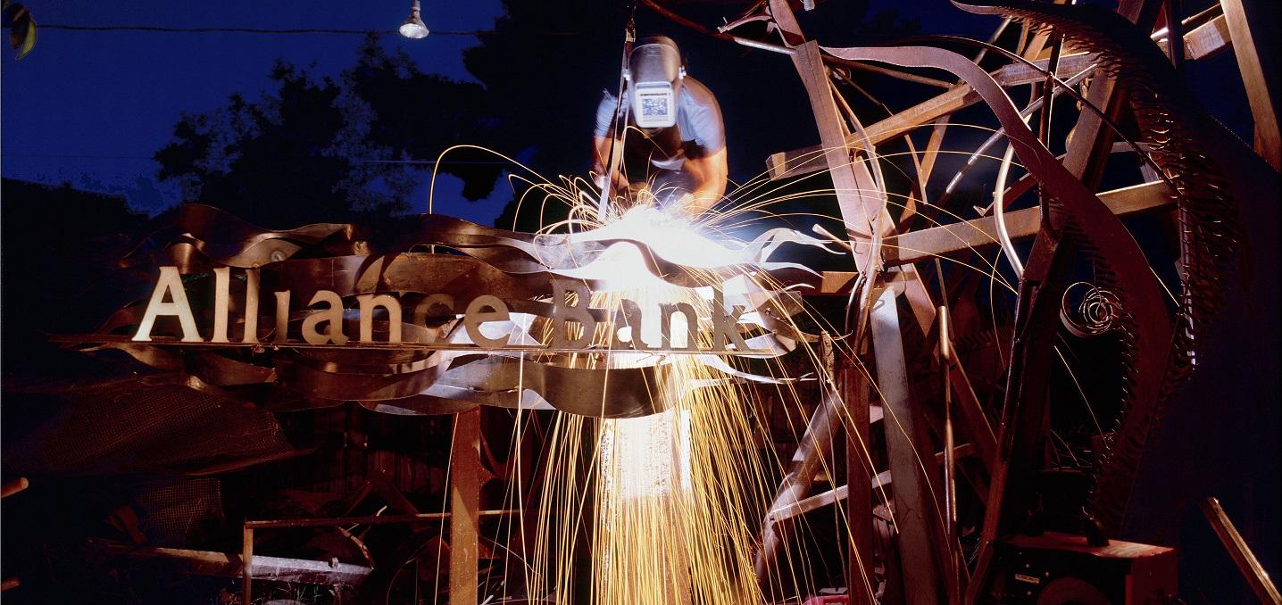 Welder making a metal sculpture outside an Alliance Bank location.