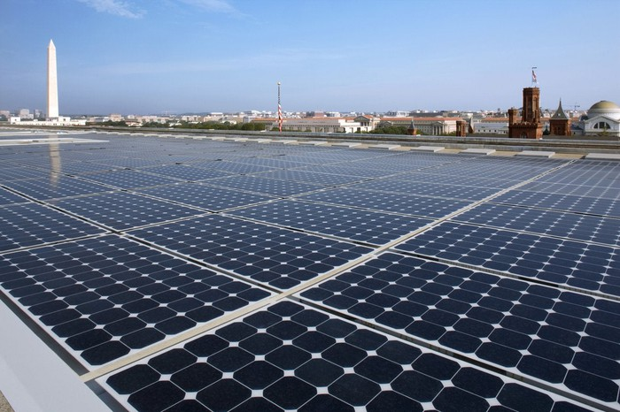 Rooftop solar installation with the Washington Monument in the background.