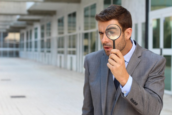 Man in a suit on the sidewalk looking through a magnifying lens.