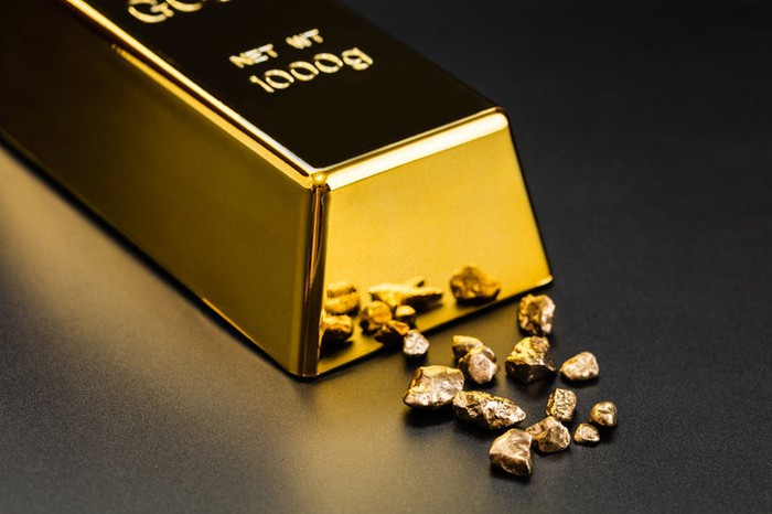 A polished gold bullion sitting next to tiny fragments of gold.