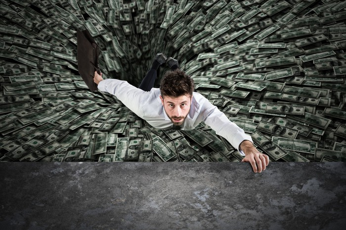Businessman being pulled into a black hole of money.