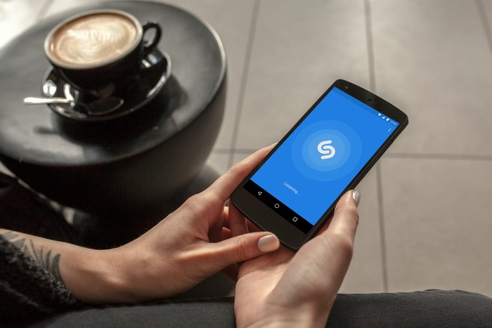Person using Shazam on a smartphone