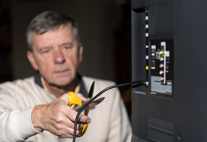Man cutting his television cable cord with a pair of scissors.