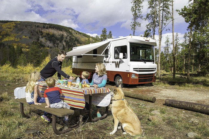 Two adults and two kids at a picnic table at a campsite, with a dog nearby, and a Winnebago RV parked in the background.