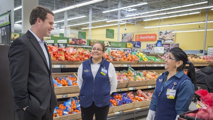 CEO Doug McMillon talks with two Walmart associates in the produce section.