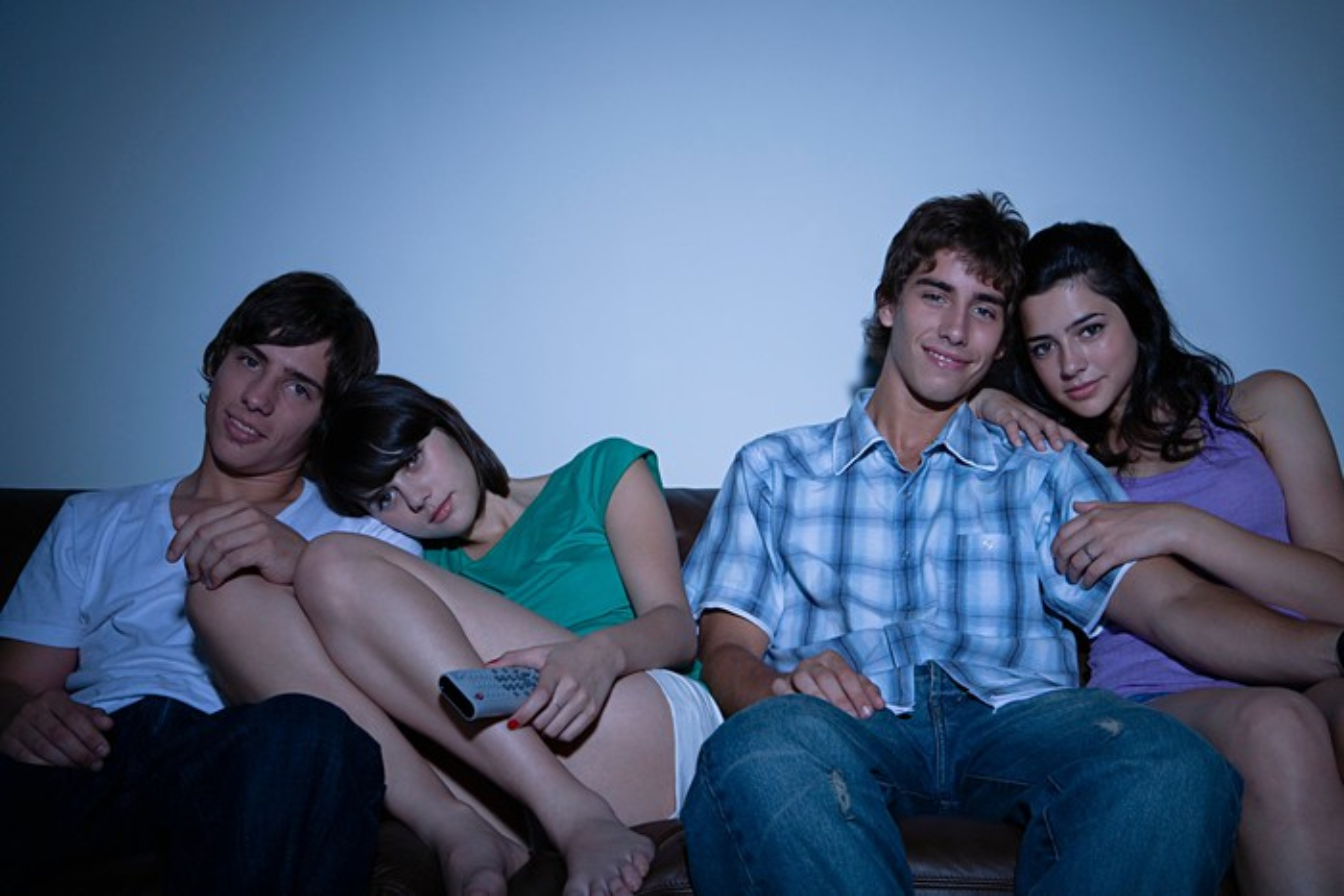 Friends watching TV in a darkened room.
