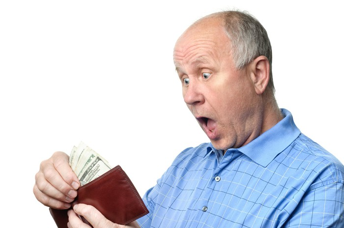 A surprised senior man looking at cash in his wallet.