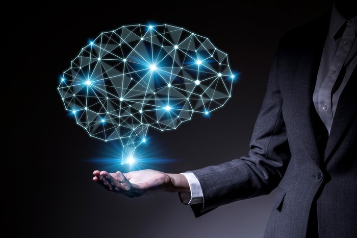 A digital representation of a human brain hovering just above the palm-up right hand of a woman who is dressed in a business suit -- concept for AI