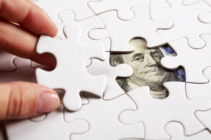 a hand placing the last piece in a white jigsaw puzzle, and it's going to cover up the face of benjamin franklin on a hundred dollar bill