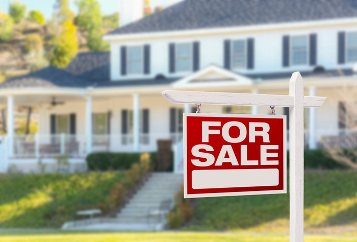A red for sale sign hangs in the yard in front of a large white house.