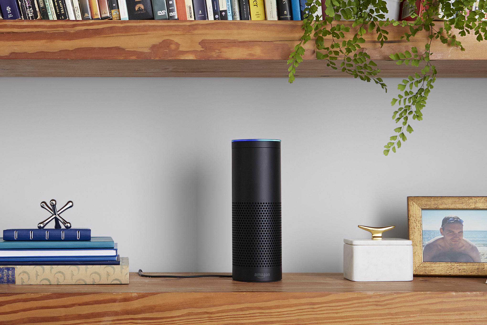 An Amazon Echo device on a bookshelf.