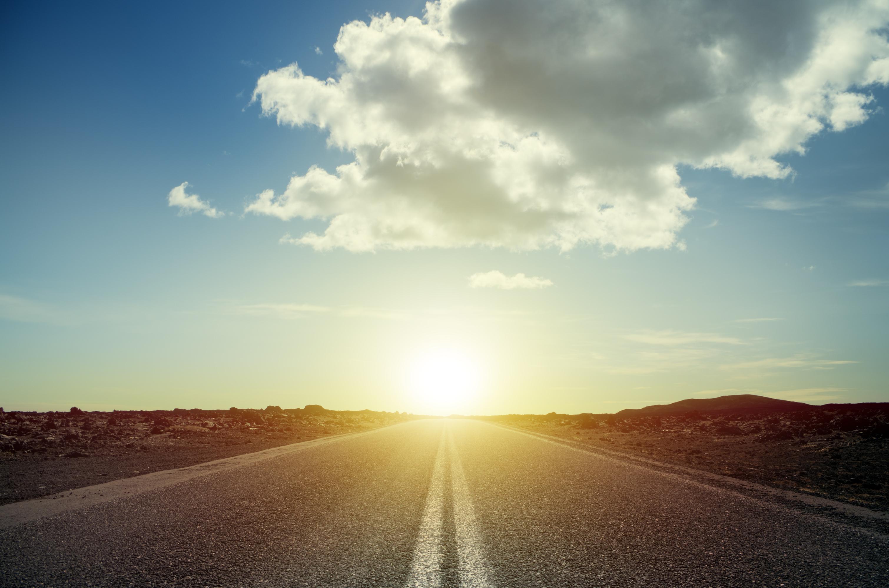 Sun setting over a road.