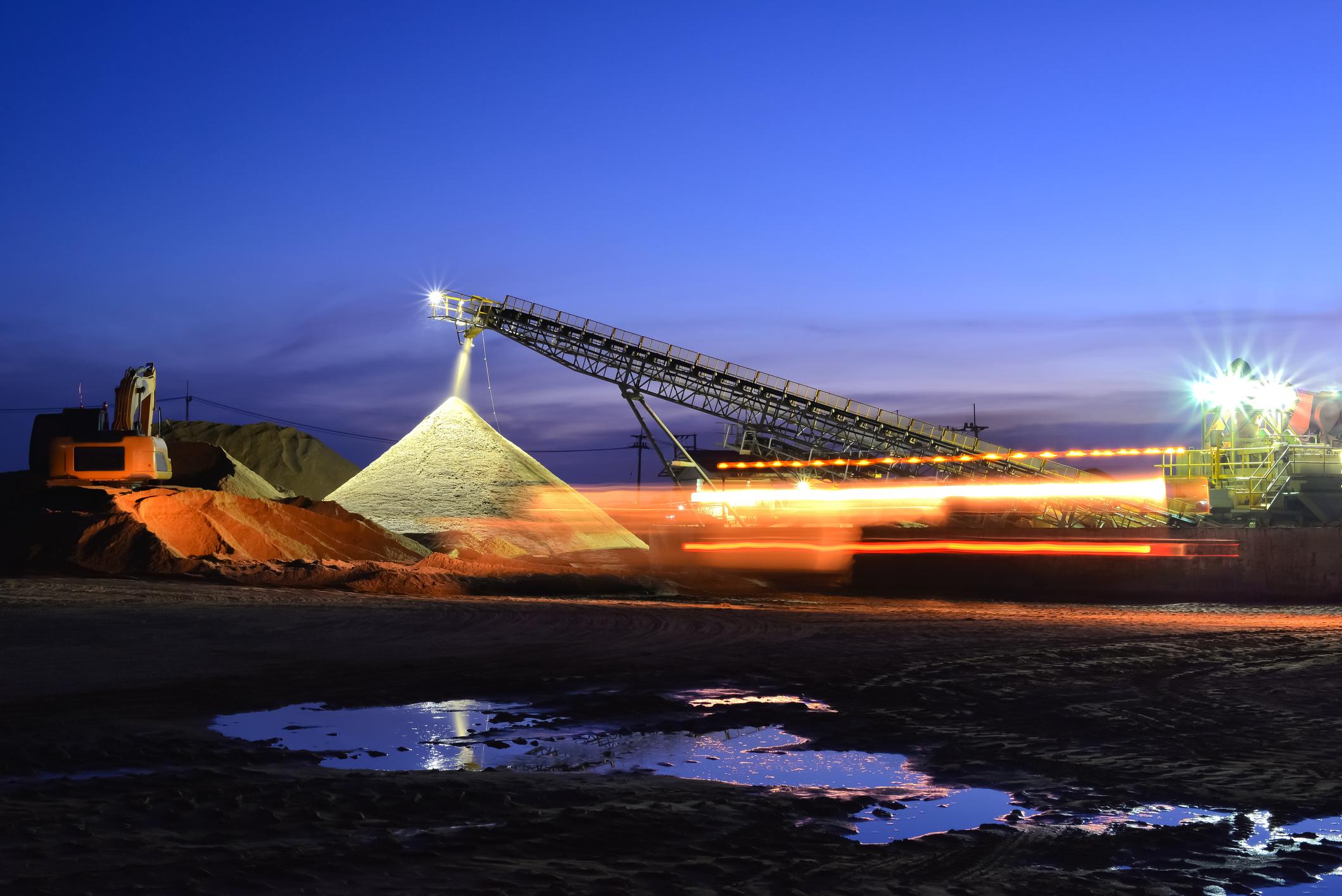 Sand mining night shift with sunset sky.