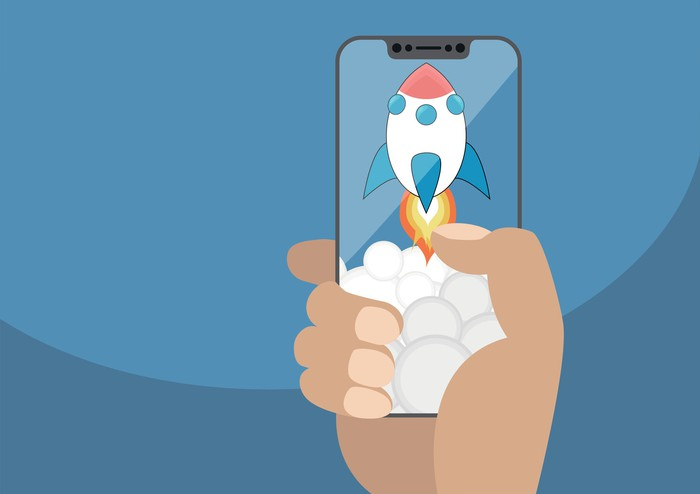 A hand holding a smartphone displaying a cartoon rocket ship taking off.