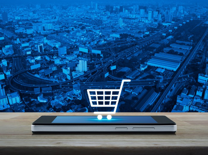A miniature shopping cart on top of a mobile phone.