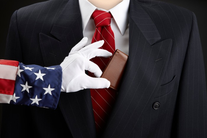 Uncle Sam grabbing a wallet from a businessman.