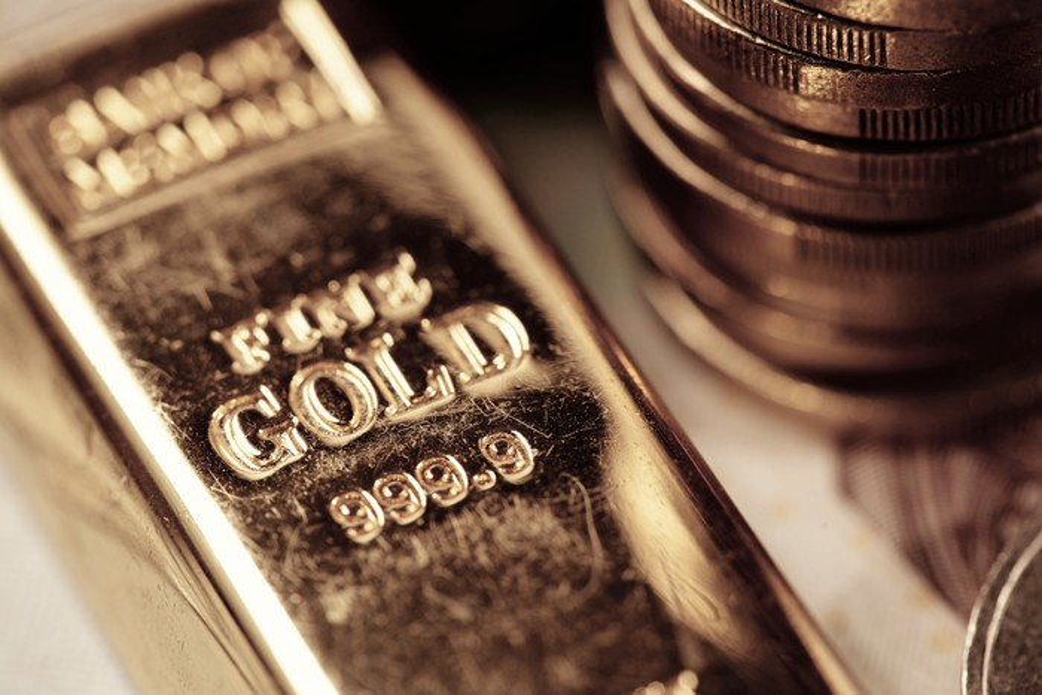 A gold bar lies next to a stack of gold coins.