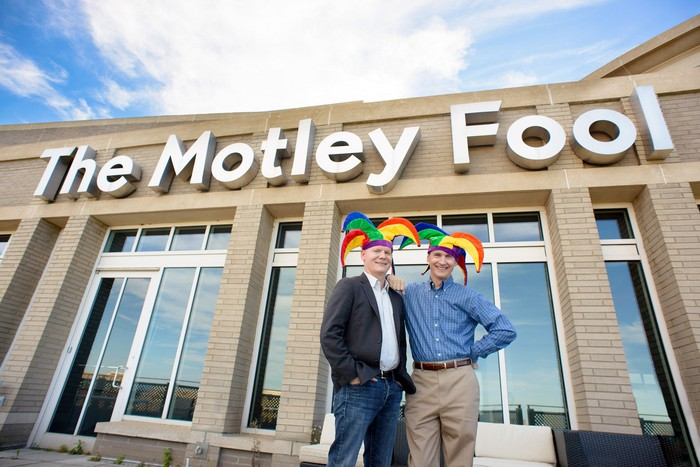 Two people wearing jester hats outside a building labeled The Motley Fool.