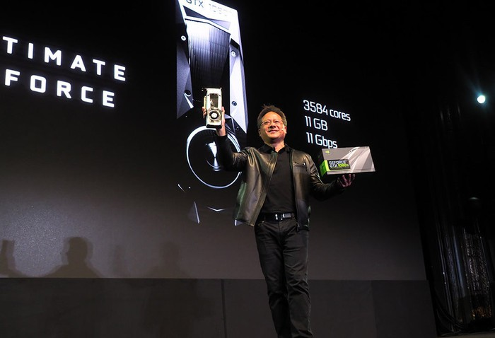 NVIDIA CEO Jensen Huang giving a presentation on a stage and holding up a graphics card in his hand.