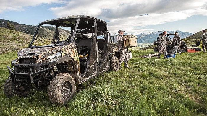 Hunters unloading a Polaris Ranger XP 1000 in a grass field