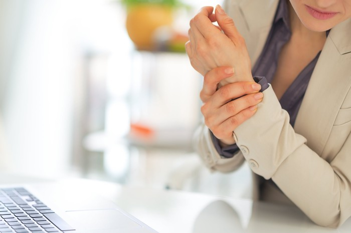 A woman sitting at a desk clutches her wrist.